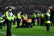 Police and stewards deal with pitch invaders at full time during the EFL Cup match between Bristol City and Manchester United at Ashton Gate, Bristol, England on 20 December 2017. Photo by Graham Hunt.