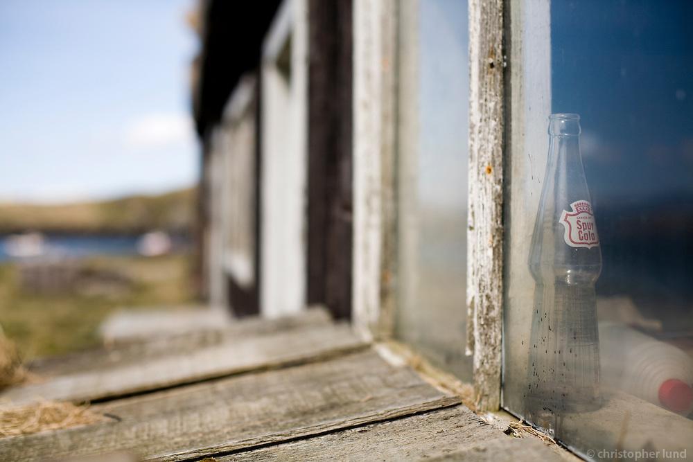 Spur Cola flaska í skemmu í Flatey.
