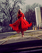 Editorial fashion photo of model Brenna Smith wearing couture dress in red lace by designer Mysterious by NPN on railroad  tracks in abandoned rice silo complex in Houston, Texas by Gerard Harrison.