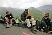 Spectators sit at the side of the road cold and wet in the high Alps. One listens on a radio telling the others how far away the riders are now.