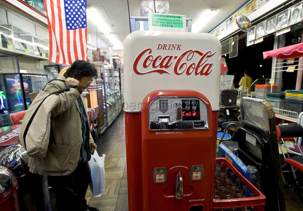 A customer looks at a 1940s-style Coca-Cola vending machine on sale at Shimura Seisakusho, a shop specializing in retro American diner goods, in the Kappabashi district of Tokyo, Japan on Nov. 10 2010. Often called Tokyo's Kitchen Town, stores in Kappabashi still mainly caters to professionals in the catering industry, though is becoming increasingly popular with foreigners hunting for unique souvenirs..Photographer: Robert Gilhooly
