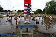 A firefighter in flag shorts looks on as a referee Monday, July 4, 2016, as two teams battle it out during the 34th annual Mud Volleyball Tournament at Raccoon River Park in West Des Moines. Twenty teams raised about $3500 for the West Des Moines firefighters association in the annual tournament.