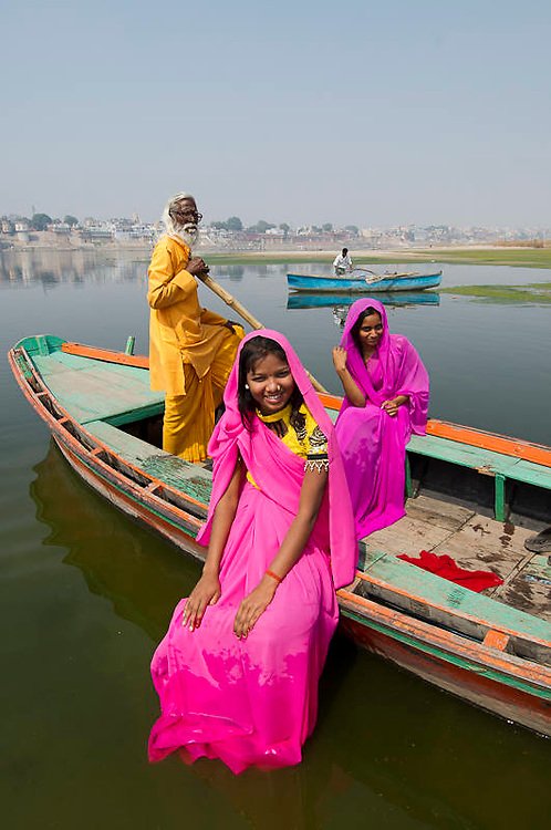 Indian women wearing bright coloured sarees in a boat on river Ganges (Ganga) in Varanasi, India
