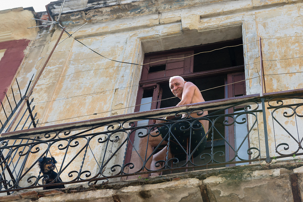Cuban man and dog on the balcony of his home in Old Havana