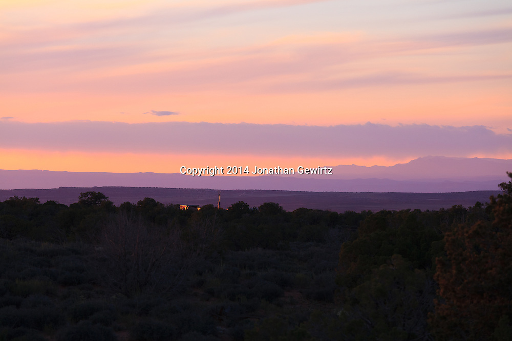 Distant structures glow red in the last rays of the setting sun in this view from the high plateau northwest of Moab, Utah.<br /> WATERMARKS WILL NOT APPEAR ON PRINTS OR LICENSED IMAGES.
