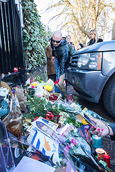 Highgate, London, December 26th 2016. Fans gather outside the London home of pop icon George Michael who died on Christmas day. PICTURED: A fan places flowers at the gate.