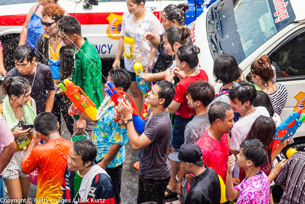 14 APRIL 2013 - BANGKOK, THAILAND:  A community water fight on Silom Road on April 14, 2013 in Bangkok, Thailand. The Songkran festival is celebrated in Thailand as the traditional New Year's Day from 13 to 15 April. The throwing of water originated as a way to pay respect to people and is meant as a symbol of washing all of the bad away. PHOTO BY JACK KURTZ