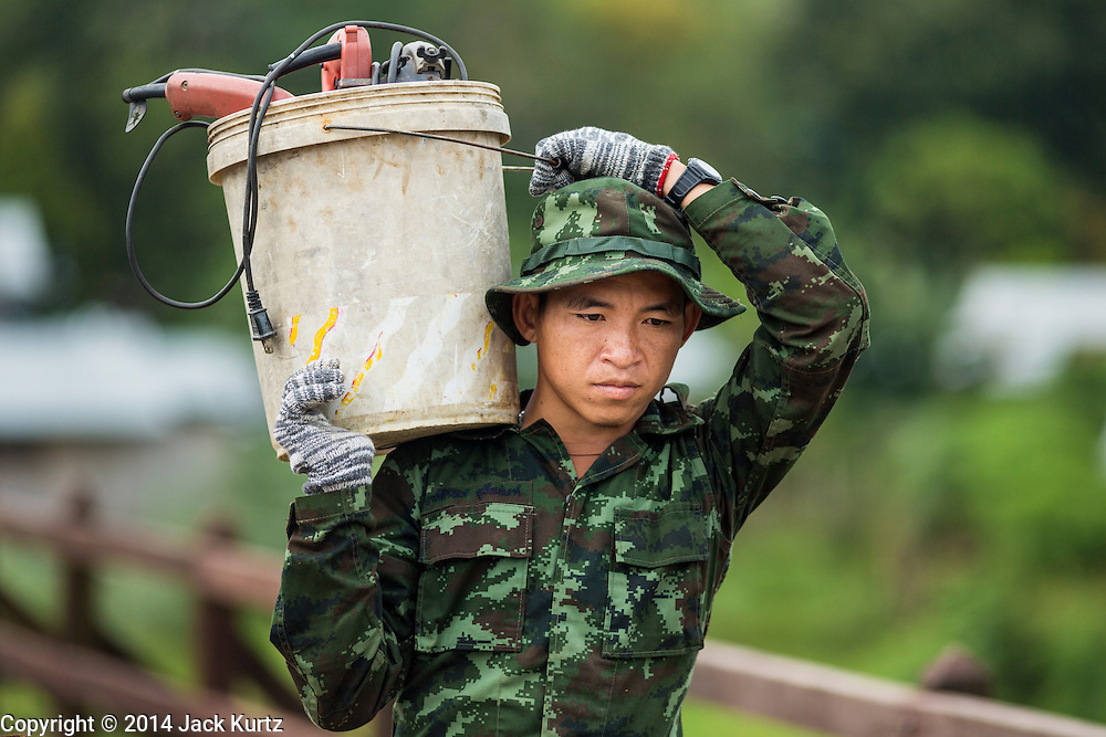 16 SEPTEMBER 2014 - SANGKHLA BURI, KANCHANABURI, THAILAND:  A soldier in the Royal Thai Army carries his tools to work on the Mon Bridge. The 2800 foot long (850 meters) Saphan Mon (Mon Bridge) spans the Song Kalia River. It is reportedly second longest wooden bridge in the world. The bridge was severely damaged during heavy rainfall in July 2013 when its 230 foot middle section  (70 meters) collapsed during flooding. Officially known as Uttamanusorn Bridge, the bridge has been used by people in Sangkhla Buri (also known as Sangkhlaburi) for 20 years. The bridge was was conceived by Luang Pho Uttama, the late abbot of of Wat Wang Wiwekaram, and was built by hand by Mon refugees from Myanmar (then Burma). The wooden bridge is one of the leading tourist attractions in Kanchanaburi province. The loss of the bridge has hurt the economy of the Mon community opposite Sangkhla Buri. The repair has taken far longer than expected. Thai Prime Minister General Prayuth Chan-ocha ordered an engineer unit of the Royal Thai Army to help the local Mon population repair the bridge. Local people said they hope the bridge is repaired by the end November, which is when the tourist season starts.   PHOTO BY JACK KURTZ