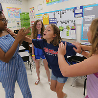 Abbey Sanders, 10, center, rushes in to interupt the conversation between Hatmony Crump, 13, left, and Ginny Parker, 10, as they go trough a improv scene during Wednesday's theater camp at Parkway Elementary School.