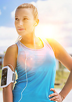 Portrait of young attractive woman standing while listening to music on her smartphone in park