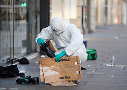 © Licensed to London News Pictures. 17/02/2019. London, UK. A police forensics officer places a shoe in an evidence bag at the scene on Oxford Street in central London where three people were stabbed last night. The incident took place near Tape Nightclub. Photo credit: Ben Cawthra/LNP