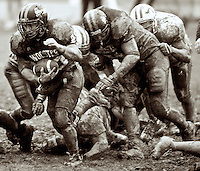 Dustin Sheppard (left) breaks through the mud and the Witt defense in the second half of Wooster's xxx to xxx win.