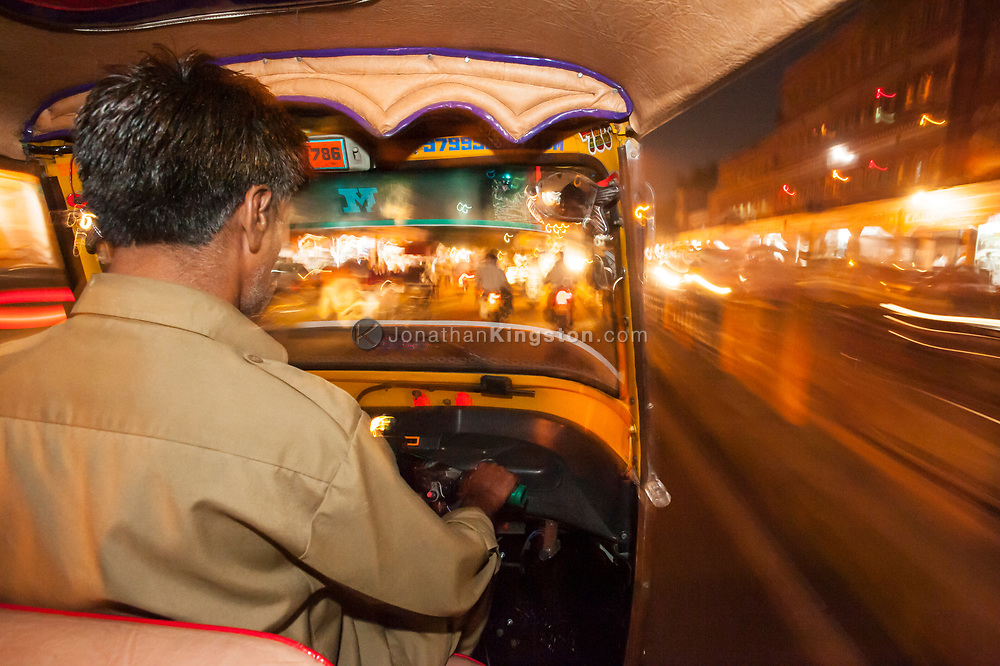 Over the shoulder view of a rickshaw driver, driving at night in India.