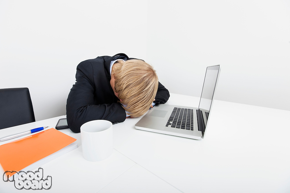 Mid adult businessman sleeping by laptop at desk in office