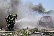 Firefighters extinguish a burning car