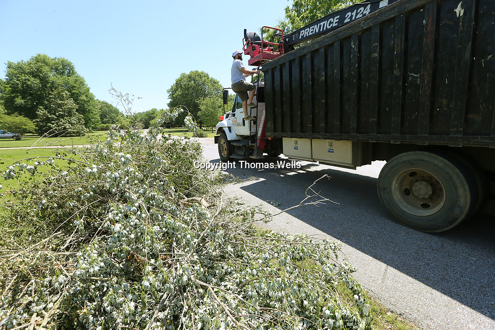 Tupelo Public Works crews begin picking up piles of debris along Countrywood Road in Tupelo on Monday.