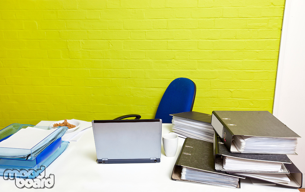 Vacant desk with laptop, folders and empty chair