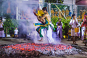 01 OCTOBER 2014 - BANGKOK, THAILAND:  A man carries a religious statue while he runs through the fire pit during the firewalking ceremony at Wat Yannawa (also spelled Yan Nawa) during the Vegetarian Festival in Bangkok. The Vegetarian Festival is celebrated throughout Thailand. It is the Thai version of the The Nine Emperor Gods Festival, a nine-day Taoist celebration beginning on the eve of 9th lunar month of the Chinese calendar. During a period of nine days, those who are participating in the festival dress all in white and abstain from eating meat, poultry, seafood, and dairy products. Vendors and proprietors of restaurants indicate that vegetarian food is for sale by putting a yellow flag out with Thai characters for meatless written on it in red.    PHOTO BY JACK KURTZ