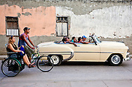 Bicitaxi and old car in Holguin, Cuba.