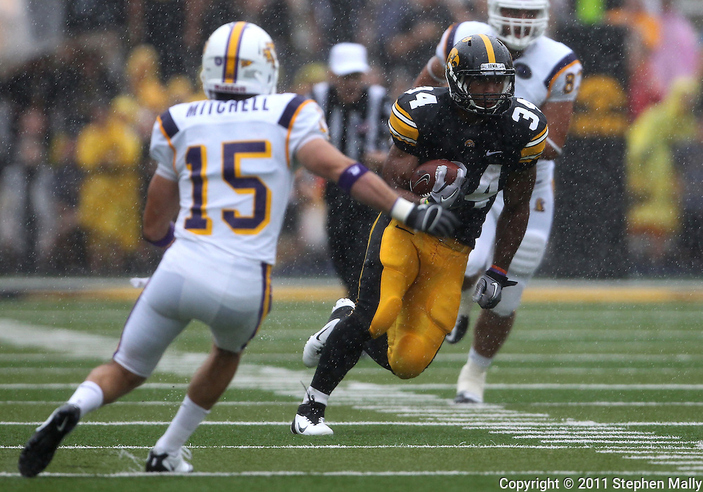 September 3, 2011: Iowa Hawkeyes running back Marcus Coker (34) tries to avoid Tennessee Tech Golden Eagles cornerback Caleb Mitchell (15) on a run during the first half of the game between the Tennessee Tech Golden Eagles and the Iowa Hawkeyes at Kinnick Stadium in Iowa City, Iowa on Saturday, September 3, 2011. Iowa defeated Tennessee Tech 34-7 in a game stopped at one point due to lightning and rain.