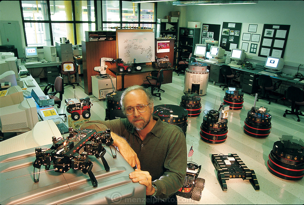 "Surrounded by the robots used in his Georgia Institute of Technology laboratory, computer scientist Ronald C. Arkin specializes in behavior-based robots, he's written a textbook with that name. Concerned more with software than hardware, he buys robots from companies and modifies their behavior, increasing their capacities. But outside such places, what Arkin calls ""the physical situatedness"" of the robot is ""absolutely crucial"" to its ability to act and react appropriately. Like many of his colleagues, he has been inspired by the way insects and other nonhuman life forms have adapted to their environment. From the book Robo sapiens: Evolution of a New Species, page 153."
