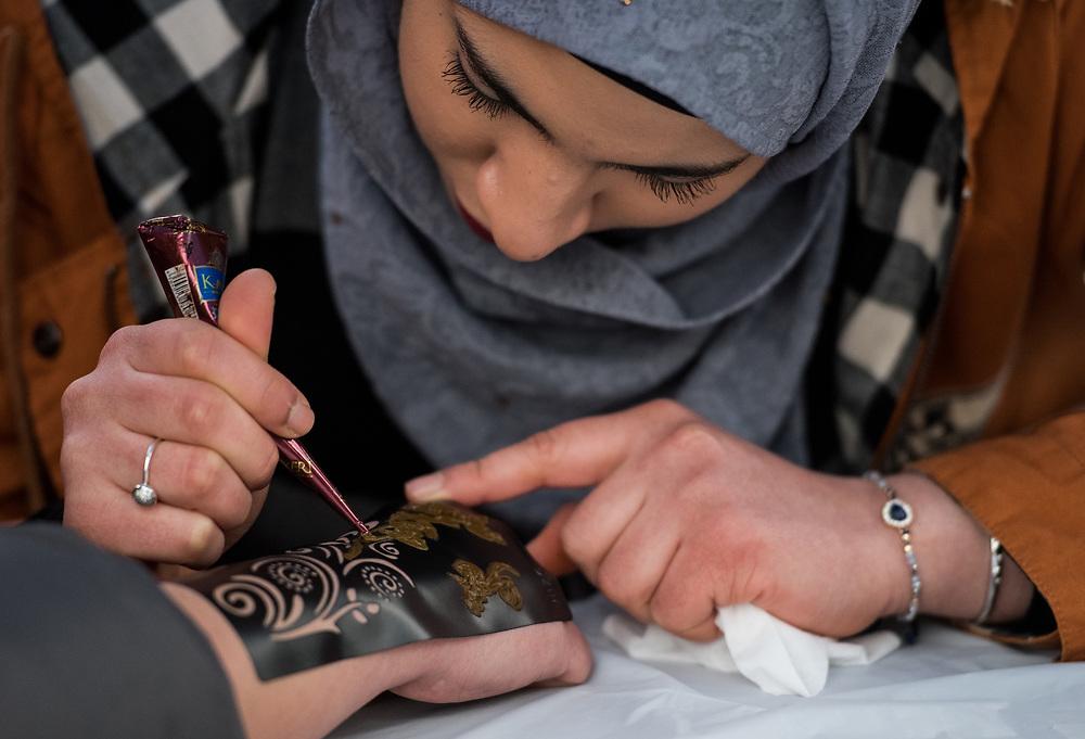 Basair Alhinai, age 22,  creates a Henna Tattoo on Adrianna Shafer's hand during the 2018 International Street Fair.