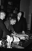 Dissolution of Dáil Eireann..1965..18.03.1965..03.18.1965..18th March 1965..The proclaimation to dissolve the Dail was signed by President Eamon de Valera and An Taoiseach Seán Lemass at a short formal ceremony at Áras an Uachtarain...Image shows An Taoiseach, Mr Sean Lemass, signing the order to dissolve his government as President DeValera watches.