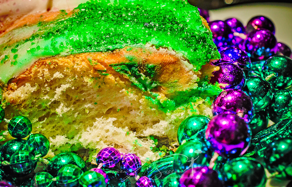 A Mardi Gras King Cake is pictured with purple and green Mardi Gras beads, March 12, 2014, in Mobile, Alabama. The king cake is traditionally made of fried or baked dough, topped with green, purple, and gold icing or sugar. Modern king cakes sometimes contain fillings such as raspberry, strawberry, cream cheese, or cinnamon. The king cake represents the three kings who visited the Christ child on Epiphany, and the cake usually includes a small plastic baby inside to represent the Christ child. French settlers held the first Mardi Gras in Mobile, Alabama in 1703. Mardi Gras is a season of revelry that extends from Epiphany, 12 days after Christmas, to Fat Tuesday, the day before Ash Wednesday and the beginning of Lent. (Photo by Carmen K. Sisson/Cloudybright).