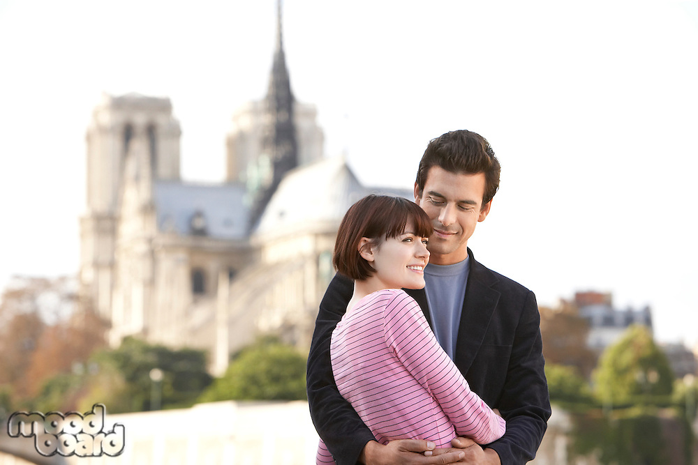 Paris France Couple embracing in front of Notre Dame Cathedral