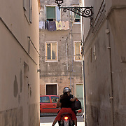 Two people riding motor scooter down narrow passageway between residential buildings in Chioggia Italy