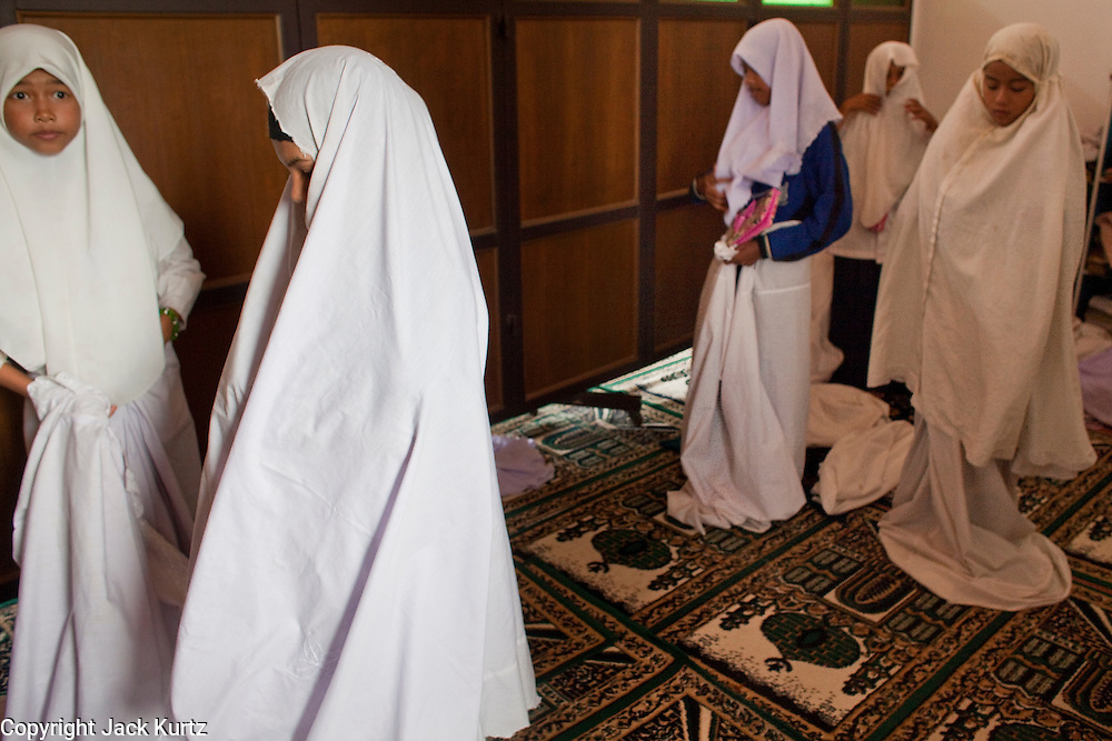 """Sept. 24, 2009 -- PATTANI, THAILAND: Thai schoolgirls prepare to pray in the Krue Se Mosque. The Krue Se Mosque is one of Thailand's most historic mosques and long a flash point in Muslim - Buddhist confrontation. The mosque was first destroyed by advancing Thais when Pattani was an independent kingdom in 1786. It was restored in the 1980's but heavily damaged by rockets fired by unknown assailants in 2005. It has since been partially restored by local Muslims and the Thai government. Thailand's three southern most provinces; Yala, Pattani and Narathiwat are often called """"restive"""" and a decades long Muslim insurgency has gained traction recently and nearly 4,000 people have been killed since 2004. The three southern provinces are under emergency control and there are more than 60,000 Thai military, police and paramilitary militia forces trying to keep the peace battling insurgents who favor car bombs and assassination.    Photo by Jack Kurtz / ZUMA Press"""