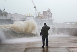 © Licensed to London News Pictures. 26/01/2016. Brighton, UK. A man braves the rain and powerful waves to venture out on the pontoon alongside Brighton Pieron January 26th 2016. Photo credit: Hugo Michiels/LNP