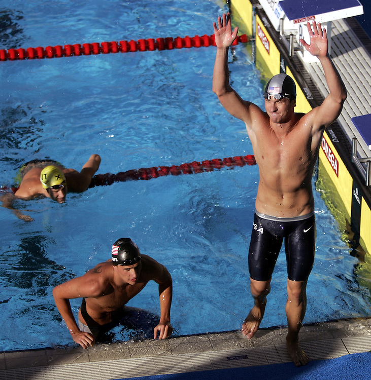 USA's Aaron Peirsol acknowledges the crowd after capturing the gold medal in the 200M backstroke as teammate and bronze medalist Ryan Lochte (L) and silver medalist Austria's Markus Rogan exit the pool at the FINA World Championships in Montreal, Canada, Friday 29 July 2005. Peirsol won in world-record time of 1:54.66.