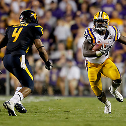 Sep 25, 2010; Baton Rouge, LA, USA; LSU Tigers running back Stevan Ridley (34) is pursued by West Virginia Mountaineers cornerback Sidney Glover (4) during the second half at Tiger Stadium. LSU defeated West Virginia 20-14.  Mandatory Credit: Derick E. Hingle