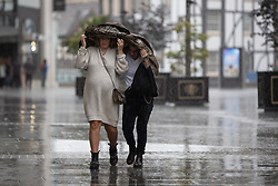 © Licensed to London News Pictures. 31/08/2019. Manchester, UK. Two women on Cathedral Street use a jacket to shelter during a heavy downpour in Manchester City Centre . Photo credit: Joel Goodman/LNP
