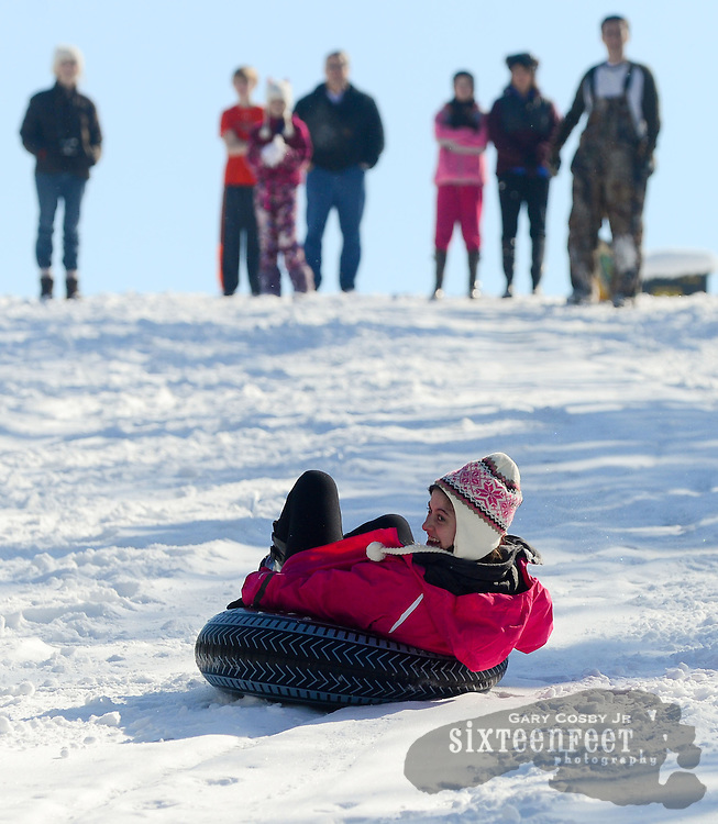Gary Cosby Jr./Decatur Daily   Snow blankets the Tennessee Valley Thursday morning after a snow that began late Wednesday and fell through much of the night.  Family and friends watch from the top of a big hill on Colony Lane in Hartselle as Danielle Owens rides an inner tube down the hill backwards.