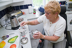 Female wheelchair user making a cup of team in her nonadapted kitchen,
