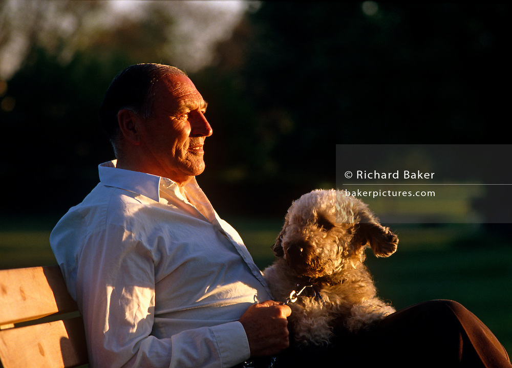 A middle-aged man, possibly in his late-fifties, holds the lead of his pet dog on a park bench in London England. Afternoon sun filters through nearby trees and the man is wearing a simple, plain white shirt. He sits crossed-legs on this warm afternoon gazing to a point in the distance looking lonely and hopeful of meeting someone else, or maybe of events in a long life. His dog is the man's best friend and companion and he guards him with a strong hand as a master should.