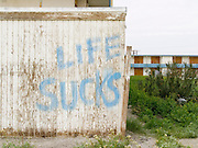 life sucks graffiti on abandoned building complex