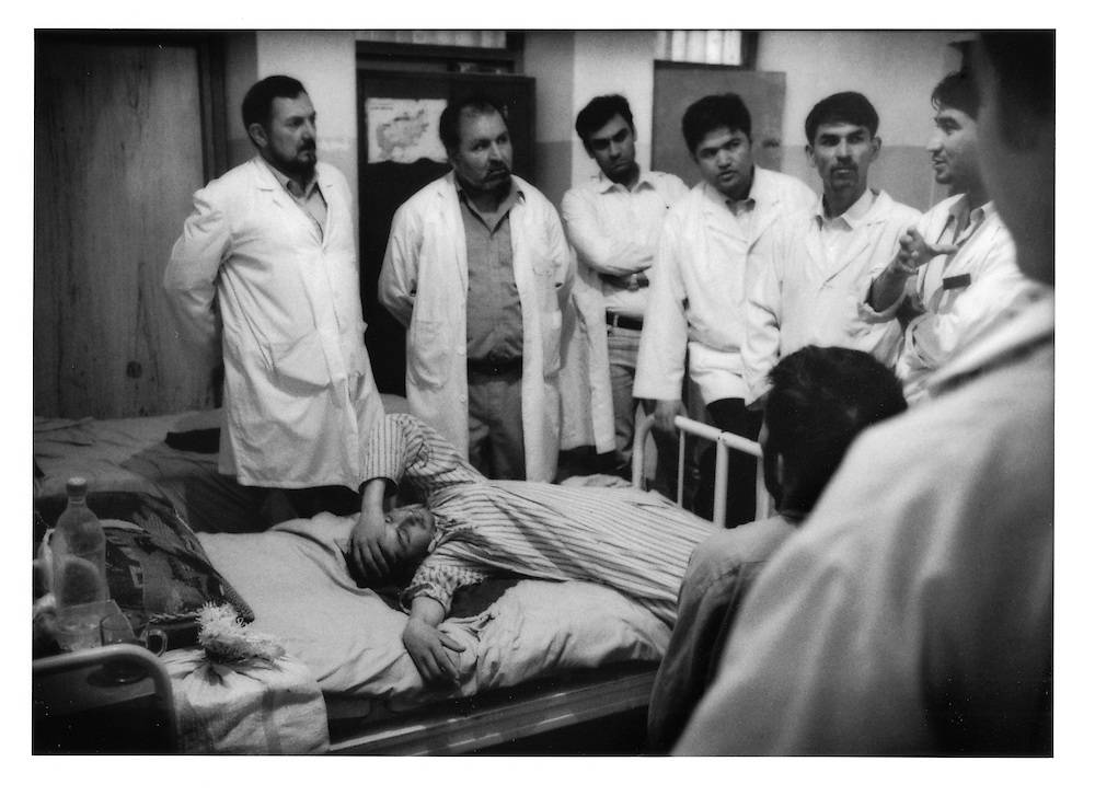 Dr. Qureshi (L), Deputy Director of  Kabul's only gov?t run mental hospital, Psychiatric and Drug Dependency Hospital, Kabul, Afghanistan listens to graduate medical student's analysis while psychiatric patient sprawls out on hospital bed, Kabul, Afghanistan.