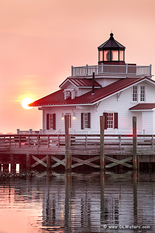 Sun rising behind the Roanoke Marshes Lighthouse in Manteo NC.