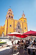 People in an outdoor cafe by the Baroque style, Parroquia de Basílica Colegiata de Nuestra Señora de Guanajuato or Guanajuato Basilica in the historic center of Guanajuato City, Guanajuato, Mexico. The massive basilica is painted bright yellow, located in along the Plaza of Peace and was built in 1671.