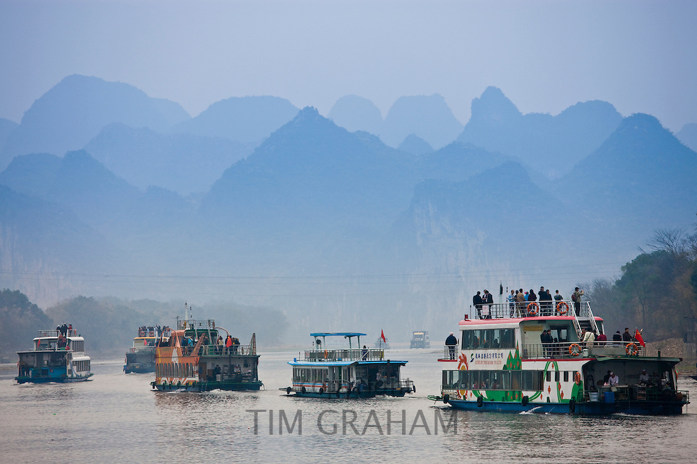 Tourist boats travel along Li River between Guilin and Yangshuo, China
