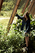 Young woman leaning against wood post in indoor garden.
