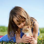 Girl 4-6 years in dress lying in field talking to tabby kitten