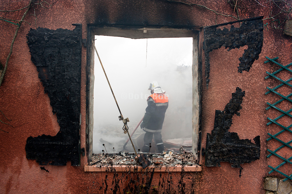 burned out house with firefighters putting out the still smoldering remains