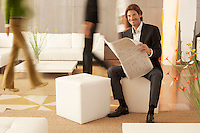 Businessman reading newspaper in lobby portrait