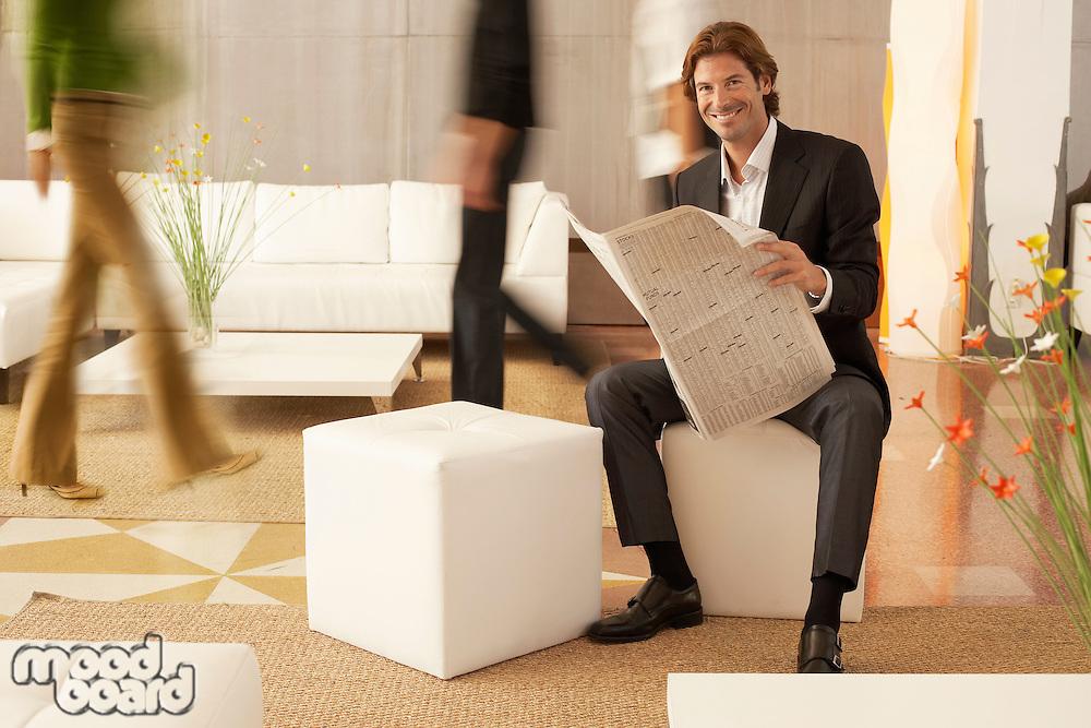 Businessman reading newspaper in lobby portrait