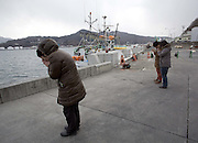 """Kamaishi, Japan - <br /> <br /> Japan 4 Years Later<br /> <br /> On March 11, 2011, a magnitude 9 earthquake struck in the Pacific Ocean about 20 miles off of the Northeastern Japanese coast of Honshu and produced a series of waves, or tsunamis, that reached 30 feet or higher. These waves slammed into a protective seawall built by the Japanese government at an estimated cost of $1.6 billion. The seawalls failed.<br /> <br /> Along the coast, more than 15,000 people lost their lives. 230,000 either lost their homes or were displaced. About 87,000 still live in temporary housing four years later.<br /> <br /> In the temporary housing near Kamaishi, Japan, about half the former residents are gone now. The Japanese government has offered subsidies of $40,000 to $60,000 to help rebuild homes that now cost $300,000 to $450,000 to rebuild, due to the shortage of construction workers and the cost of building materials. Some have moved in with relatives; others moved into permanent apartments and manyhave simply left the area for good.<br /> <br /> Tokyo has set aside $155 billion to rebuild, and yet many in Kamaishi wonder where the money is going. Some of it is spent on schemes to literally raise the ground up to 15 feet in devastated towns like Otsuchi and Rikuzentakata City, which were practically flattened by the tsunami. Even more is being spent to repair the failed seawall.<br /> <br /> Despite efforts by Tokyo to raise the ground level and repair the sea walls, many people in the area are losing hope of having their lives back. Takemi Wada, who lost her home and mother at Rikuzentakata City, said she'll never move back even with the elevated land. """"Who wants to live on top of a graveyard?"""" she asked.<br /> <br /> Photo shows:  Japanese stop and pay their respects at the Kamaishi port during a moment of silence at 2:46 pm, the moment the earthquake struck the region four years ago. Kamaishi suffered great loss of life and damage from the tsunami resulting from the ear"""