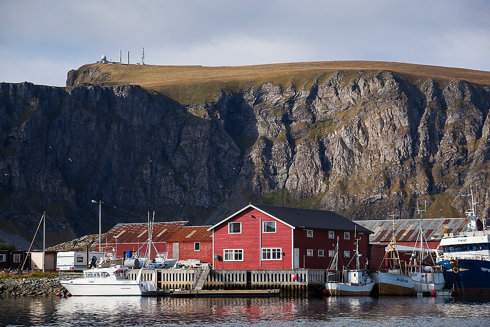Commercial fishing boats and warehouses in Sorland, Vaeroy Island, Lofoten Islands, Norway. The North Atlantic Treaty Organization (NATO) naval military radar is visible on the plateau above.